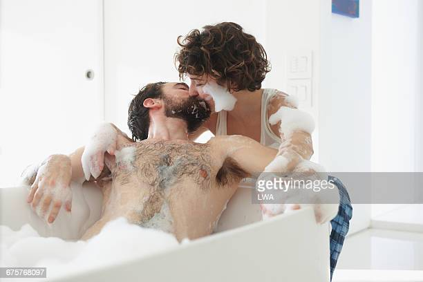 woman kissing man in bubble bath - couple and kiss and bathroom stock photos and pictures