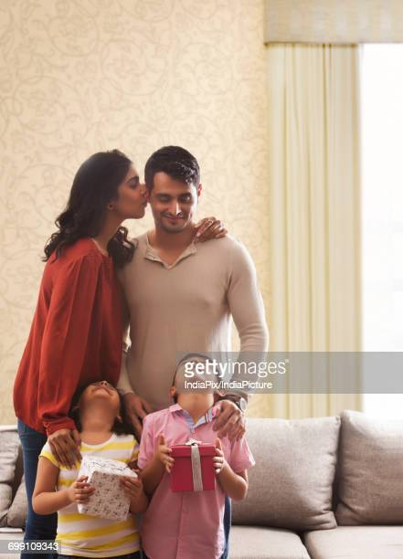 """woman kissing man on cheek, girl and boy holding gifts looking up with heads back "" - indian girl kissing stock photos and pictures"