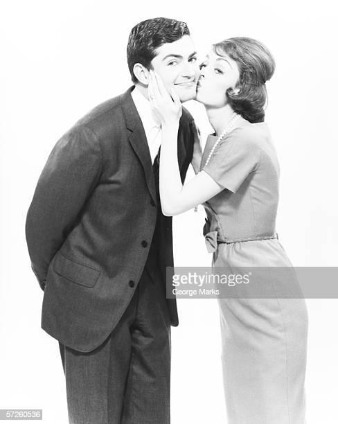 Woman kissing man on cheek in studio, (B&W)