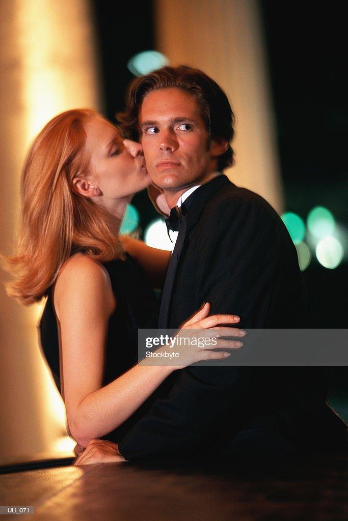 Woman kissing man on cheek, man turning head : Stock Photo