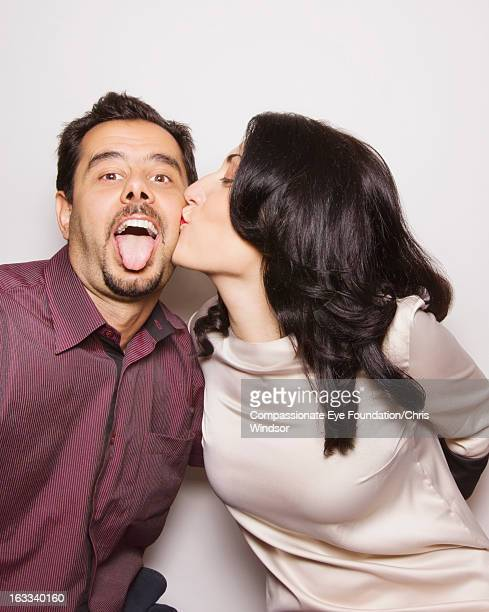 woman kissing man on cheek - couple tongue kissing stock photos and pictures
