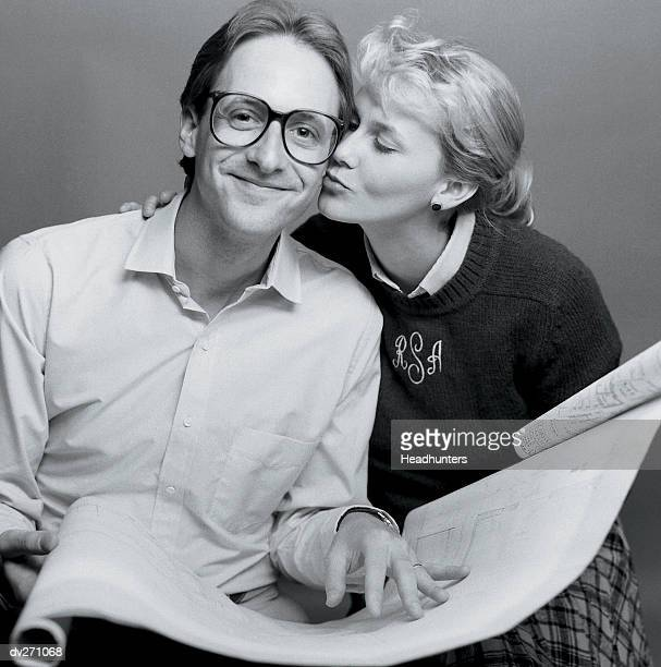 woman kissing man on cheek - headhunters stock pictures, royalty-free photos & images
