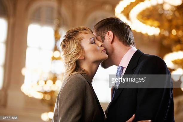 woman kissing man on the cheek - cheek stock pictures, royalty-free photos & images