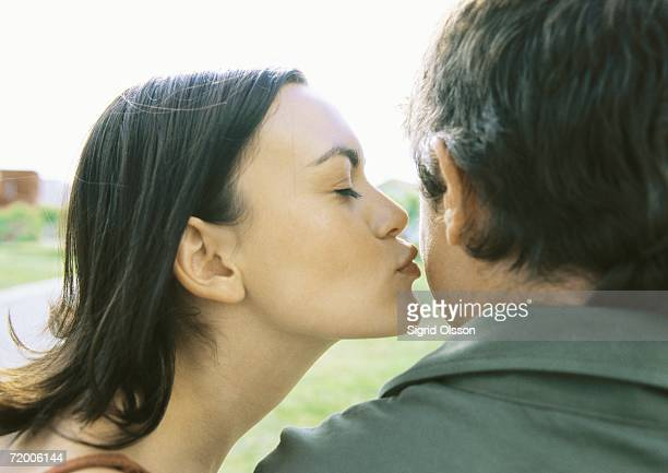 woman kissing man's cheek - cheek stock pictures, royalty-free photos & images