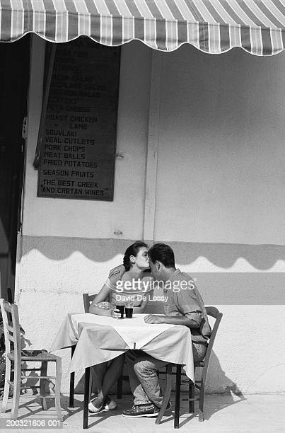 woman kissing man's forehead at outdoor cafe (b&w) - carinhoso imagens e fotografias de stock