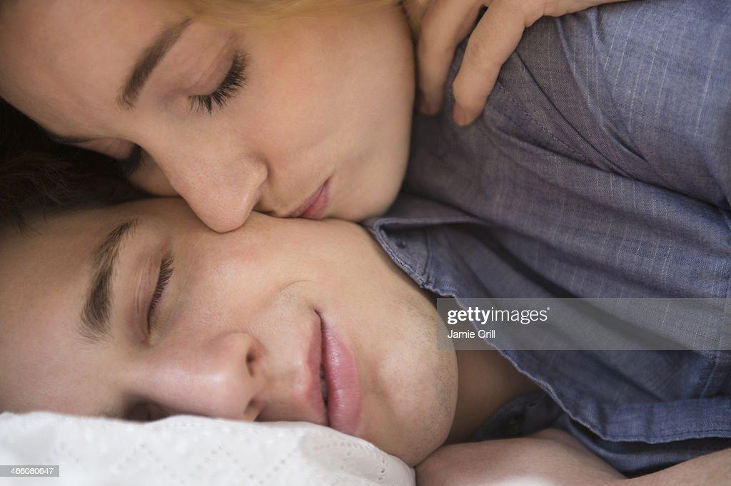 Woman kissing sleeping boyfriend