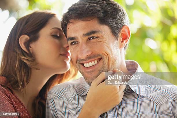 Woman kissing smiling husband outdoors