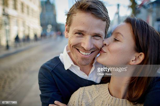 Woman kissing smiling man outdoors