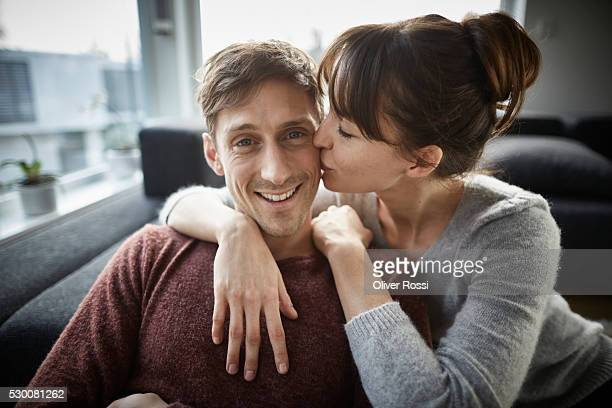 woman kissing smiling man's cheek - cheek stock pictures, royalty-free photos & images