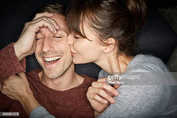 Woman kissing smiling man's cheek