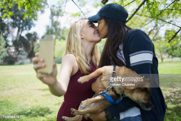 woman kissing while taking selfie with dog at park - lesbica bacio foto e immagini stock