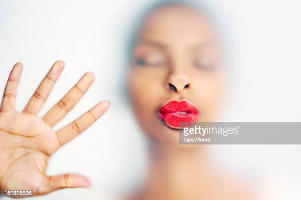 Woman kissing with face pressed against  glass