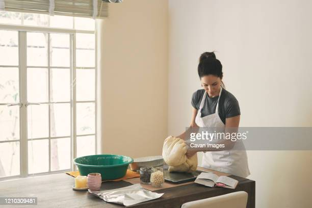 woman kneading dough while reading recipe in book at table - baking bread stock pictures, royalty-free photos & images