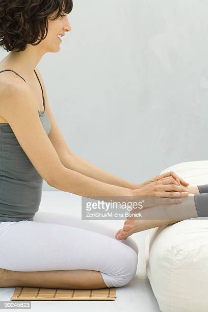 Woman kneeling at foot of futon massaging another woman's feet