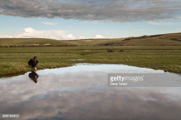Woman kneeling down and gazing at her reflection in large puddle of water in wide landscape