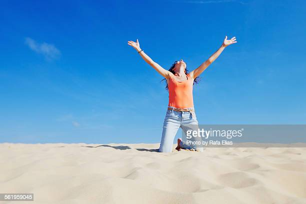 Woman kneeling down on dune with arms raised