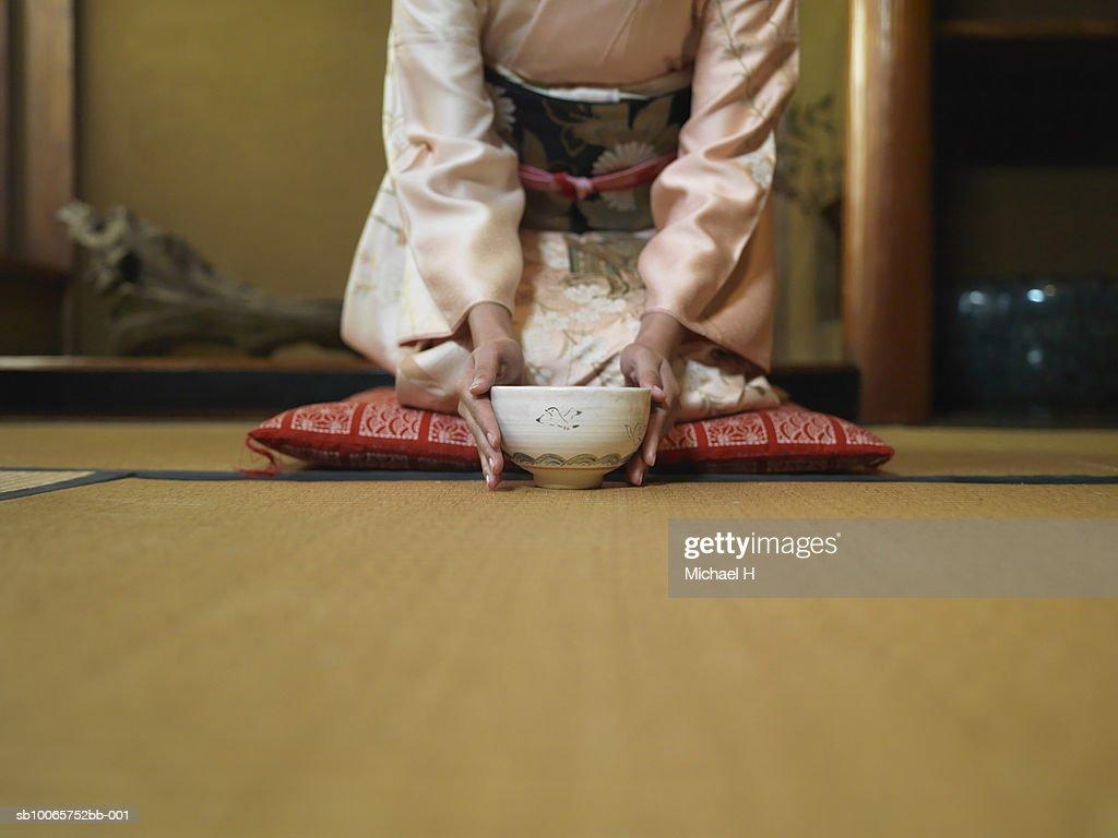Woman kneeling down tea bowl, mid section : Stock Photo