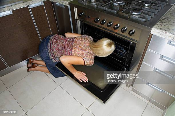 a woman kneeling down to look at an oven. - down blouse stock-fotos und bilder