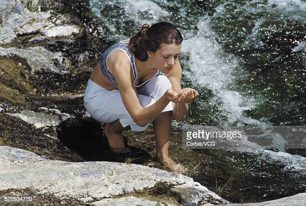 woman kneeling in a rocky bay - vcg stock pictures, royalty-free photos & images