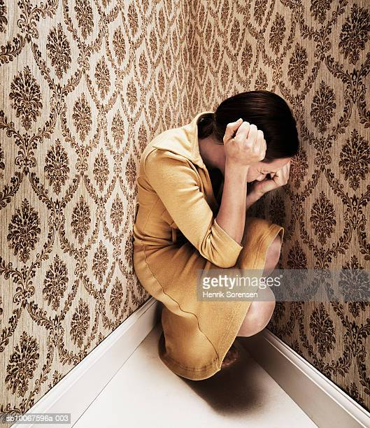 woman kneeling in corner with head in hands - derrota imagens e fotografias de stock