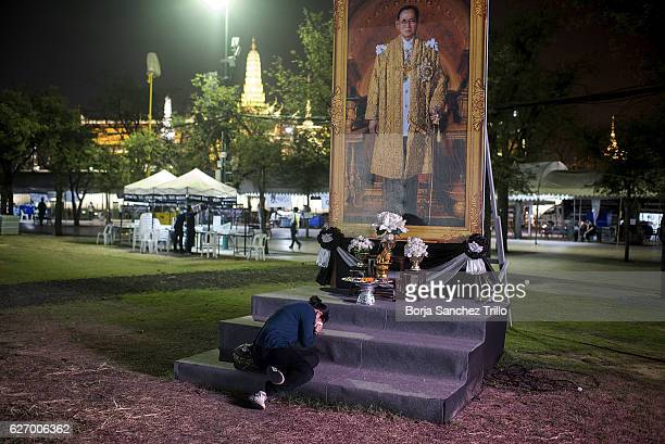 A woman kneeling in front of late King Bhumibol Adulyadej's portait at the Grand Palace during a ceremony in his honour led by Thailand's Crown...