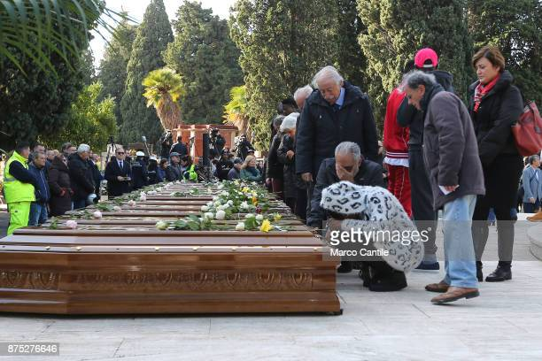 A woman kneeling in front of the coffins during the funeral of the 28 migrant women who died in a shipwreck as they sought to reach Italy