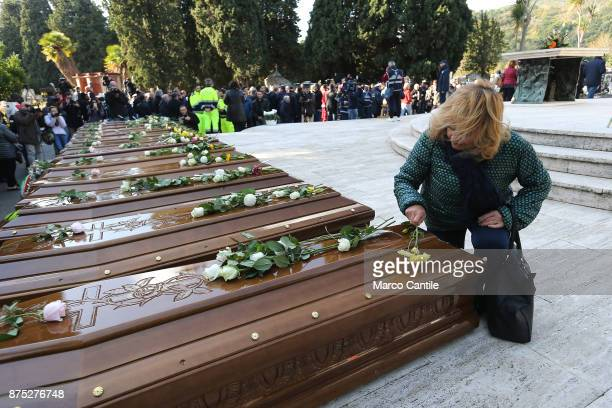 A woman kneeling in front of the coffins leaves a flower during the funeral of the 28 migrant women who died in a shipwreck as they sought to reach...