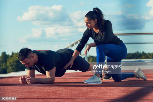 woman kneeling next to man doing plank position - all weather running track stock pictures, royalty-free photos & images