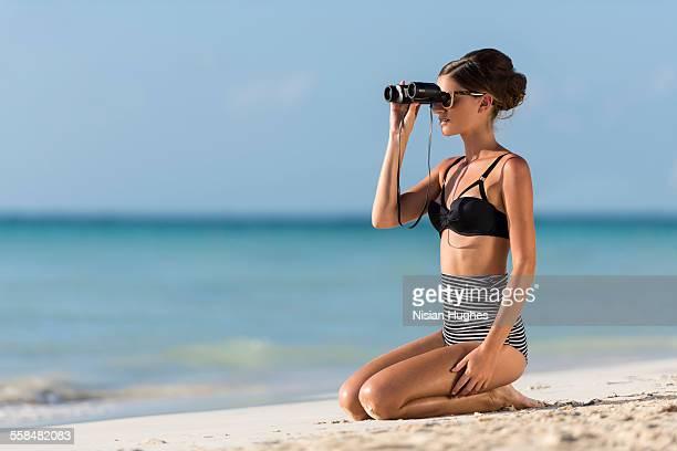 woman kneeling on beach with binoculars