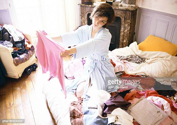woman kneeling on bed among clothes - messy stock pictures, royalty-free photos & images