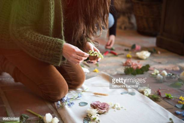 Woman kneeling on floor arranging flower heads and stems on textile, mid section