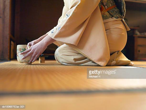 Woman kneeling on floor, preparing tea, side view