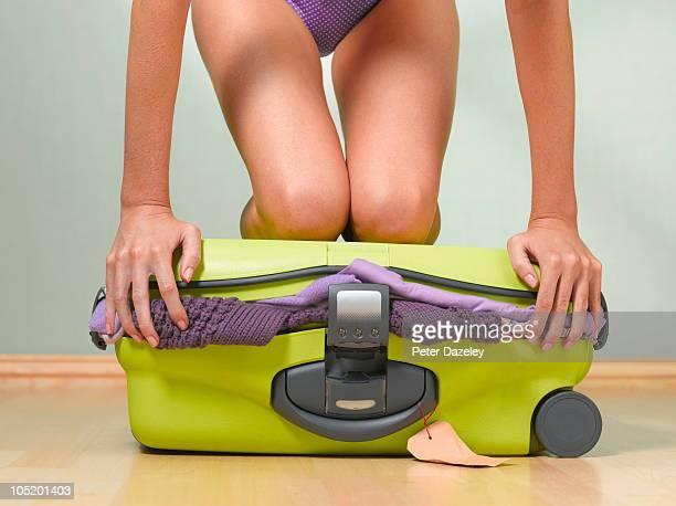 Woman kneeling on full suitcase