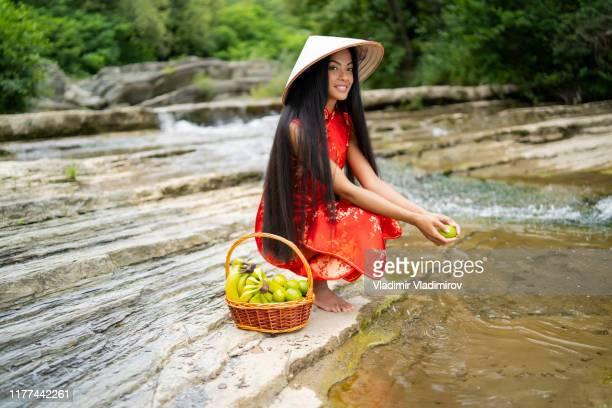 femme s'agenouillant sur la rivière et lavant des fruits - chapeau chinois photos et images de collection