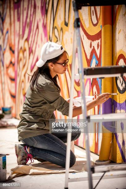 Woman kneeling on tarp painting mural on wall