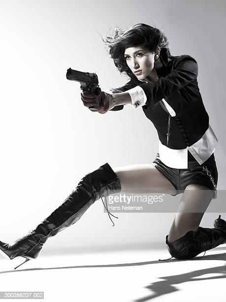 Woman kneeling, pointing gun, close-up