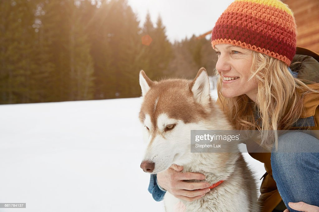 Woman kneeling with husky in snow covered landscape, Elmau, Bavaria, Germany : Stock Photo