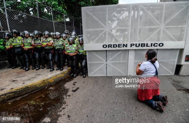 A woman kneels during an opposition march in a quiet show of condemnation of the government of President Nicolas Maduro in Caracas on April 22...