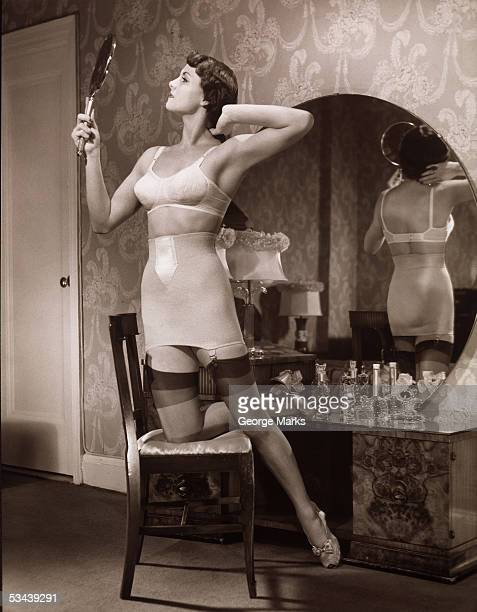 A woman kneels in a chair dressed in her brassiere and stockings admiring herself in a hand mirror and arranging her hair 1940s