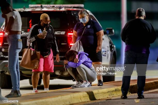 Woman kneels on the ground outside the University of Chicago Medicine's Comer Children's Hospital where a 8-year-old girl was taken after being...