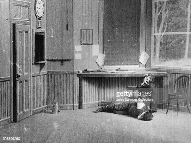A woman kneels over the bound and gagged telegraph operator in a scene from The Great Train Robbery Filmed in 1903 the movie is an innovative...