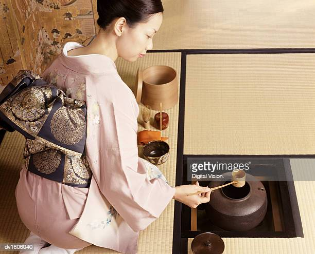 Woman Kneels Scooping Water From a Bowl During a Japanese Tea Ceremony