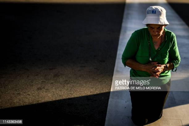 TOPSHOT A woman kneels to pray at the Fatima shrine in Fatima central Portugal on May 12 2019 Thousands of pilgrims converged on the Fatima Sanctuary...