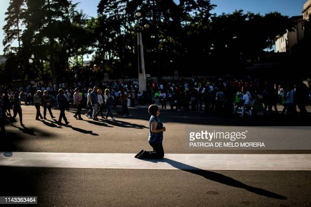 Woman kneels to pray at the Fatima shrine in Fatima, central Portugal, on May 12, 2019. - Thousands of pilgrims converged on the Fatima Sanctuary to...