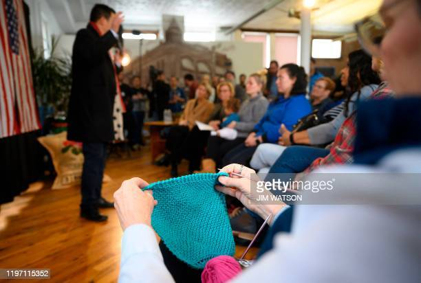 A woman knits as she listens to Democratic presidential candidate Andrew Yang speaks during a town hall meeting in Perry Iowa on January 28 2020 Yang...