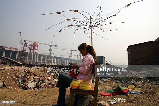 A woman knits in front of the Three Gorges Dam before a ceremony to celebrate the completion of concrete placement of the Dam on May 20 2006 in...