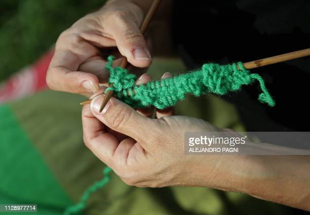 A woman knits parts of a flag that will be used at an international women meeting in Parque Patricios Buenos Aires on February 24 2019 The fabrics...