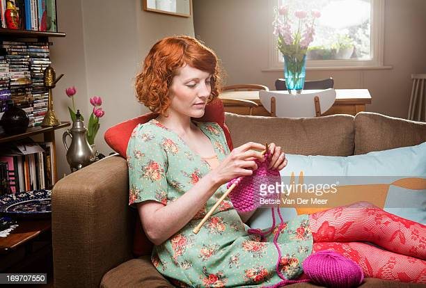 Woman knitting, sitting in livingroom.