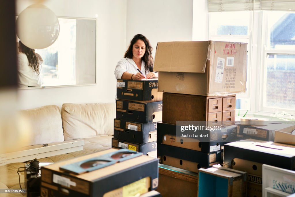 Woman labelling boxes in the process of packing to move house : Stock Photo