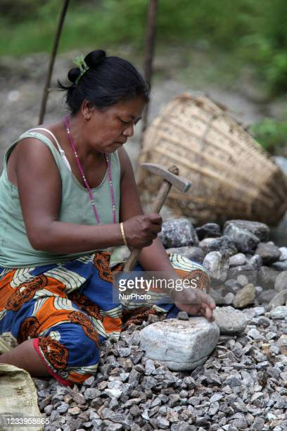 Woman laborer breaks rocks into smaller stones which she will sell for use in cement and building construction in Khechuperi, Sikkim, India, on June...